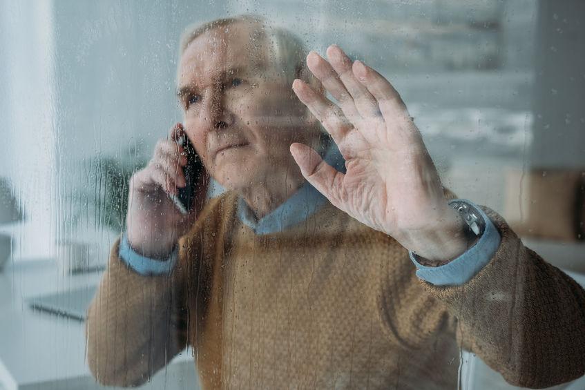 Magányos idősebb úr az ablakban.