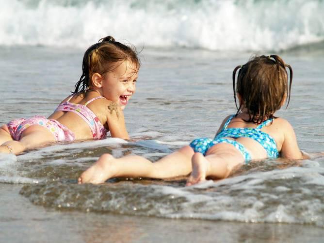 Pancsoló, napfürdőző gyerekek a tengerparton