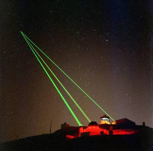 Zöld lézersugarak az éjjeli égbolton
